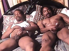 Twosome morose and roasting dark skinned studs masturbate together on the bed